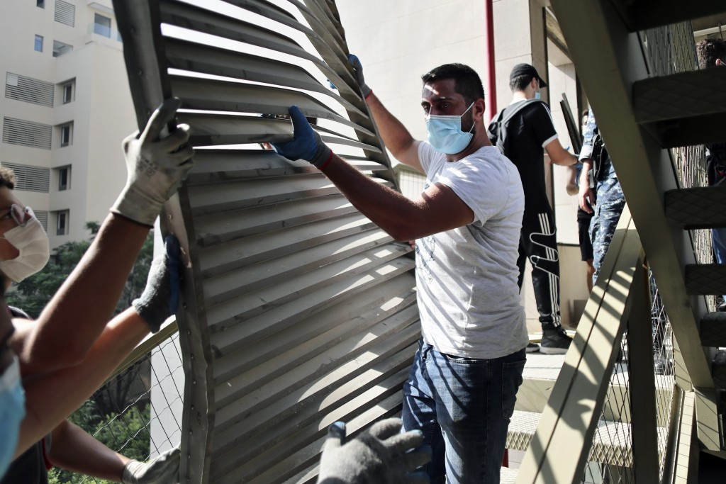 FILE - In this August 7, 2020 file photo, people remove debris from the damaged Rosary Sisters Hospital in a neighborhood near the scene of the Aug. 4...