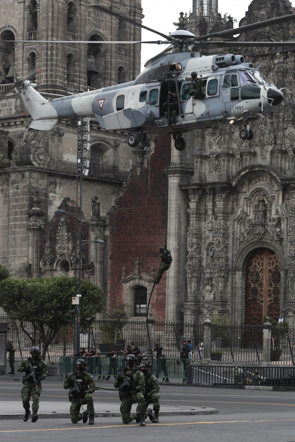 A paratrooper repels from a helicopter hovering over Mexico City's main square, known as the Zocalo, during the annual Independence Day military parad...