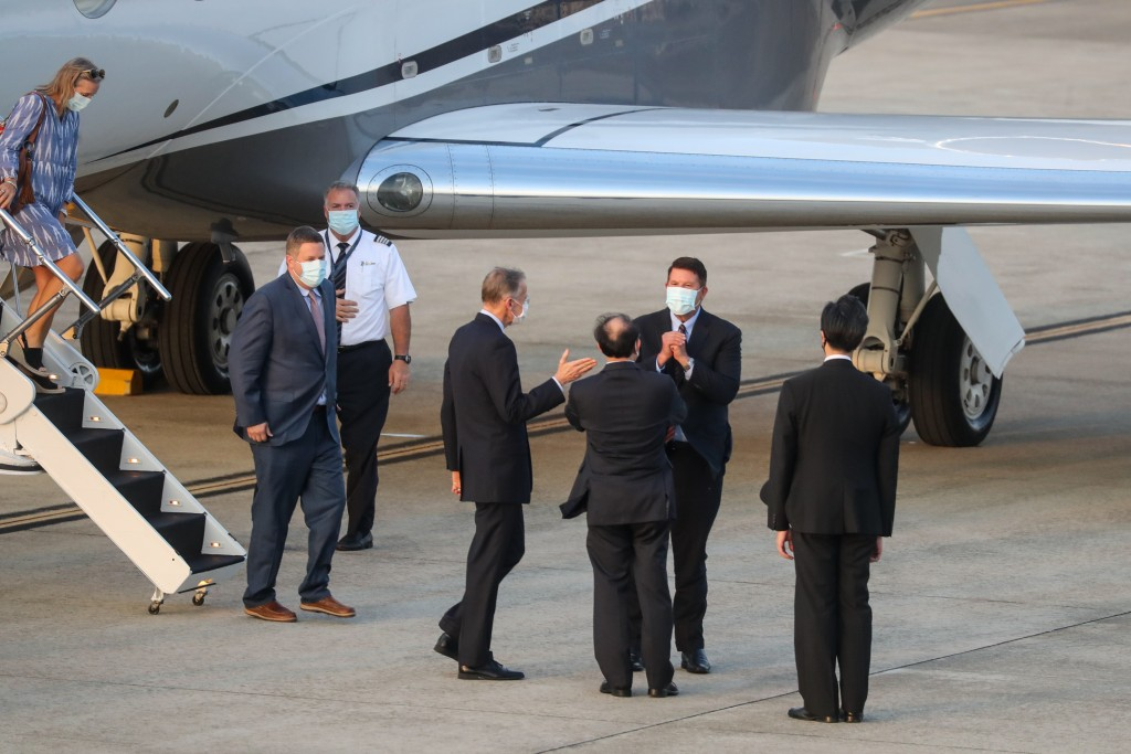 U.S. Under Secretary of State Keith Krach, second right, reacts as he is greeted after disembarking from a plane upon arrival at the airport in Taipei...