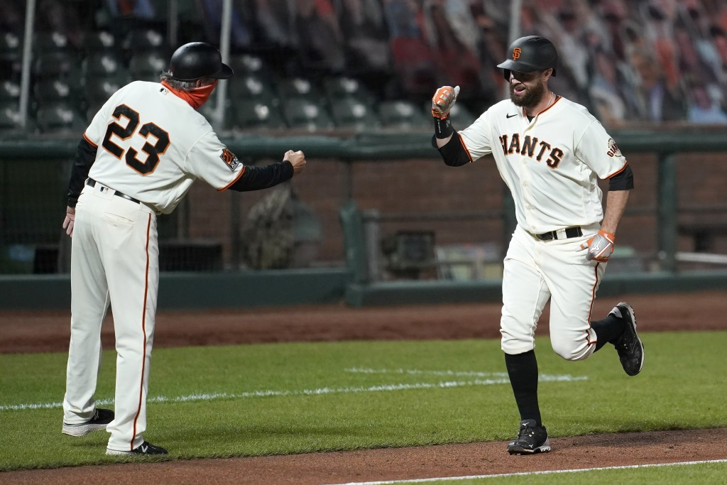 San Francisco Giants' Brandon Belt, right, is congratulated by third base coach Ron Wotus after hitting a two-run home run against the Seattle Mariner...