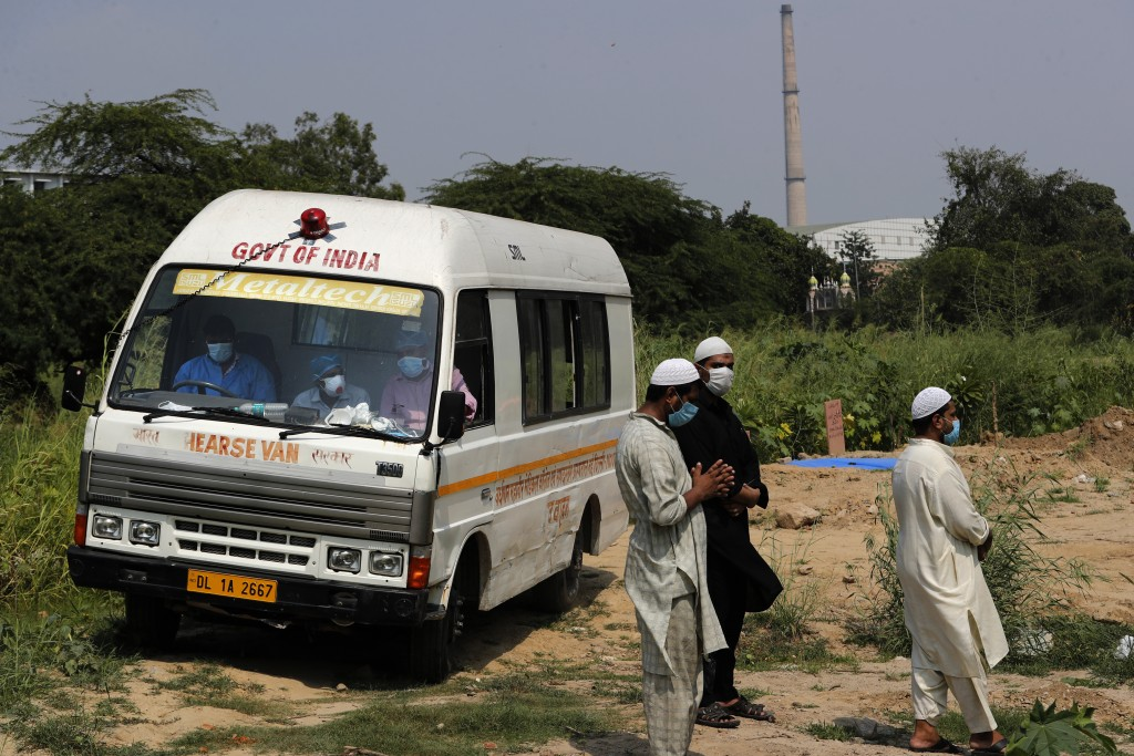 An ambulance leaves after delivering the body of a COVID-19 victim at a graveyard in New Delhi, India, Wednesday, Sept. 16, 2020. India is now second ...