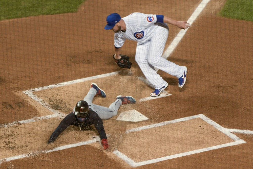 Cleveland Indians' Francisco Lindor (12) slides safely into home around Chicago Cubs starting pitcher Jon Lester  during the first inning of a basebal...