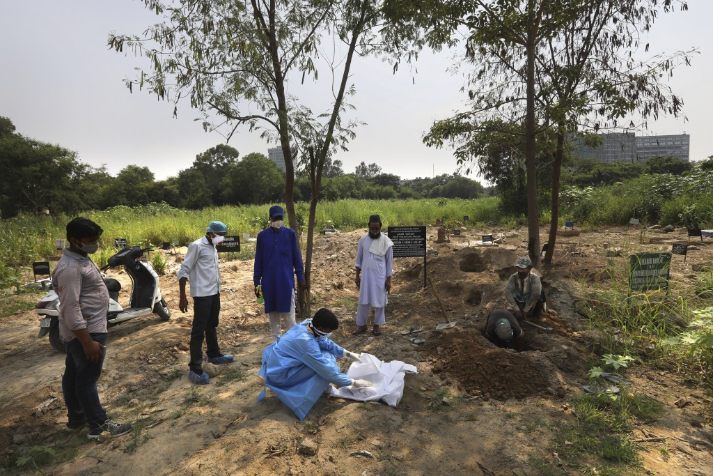 A man wearing personal protective equipment places the body of his three-month-old son who died of COVID-19 for burial in New Delhi, India, Wednesday,...