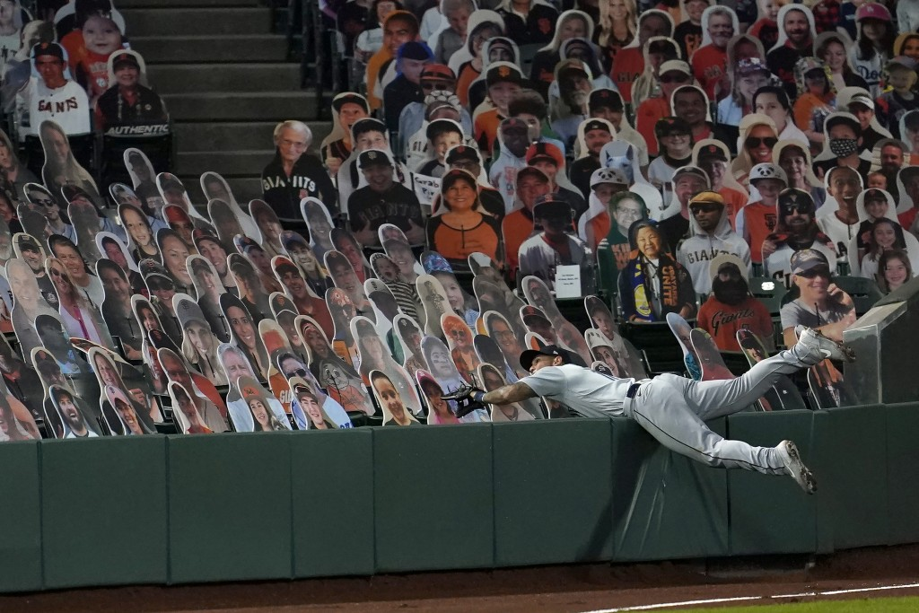 Seattle Mariners left fielder Tim Lopes reaches into seats occupied by cutouts while unsuccessfully trying to catch a foul by hit by San Francisco Gia...