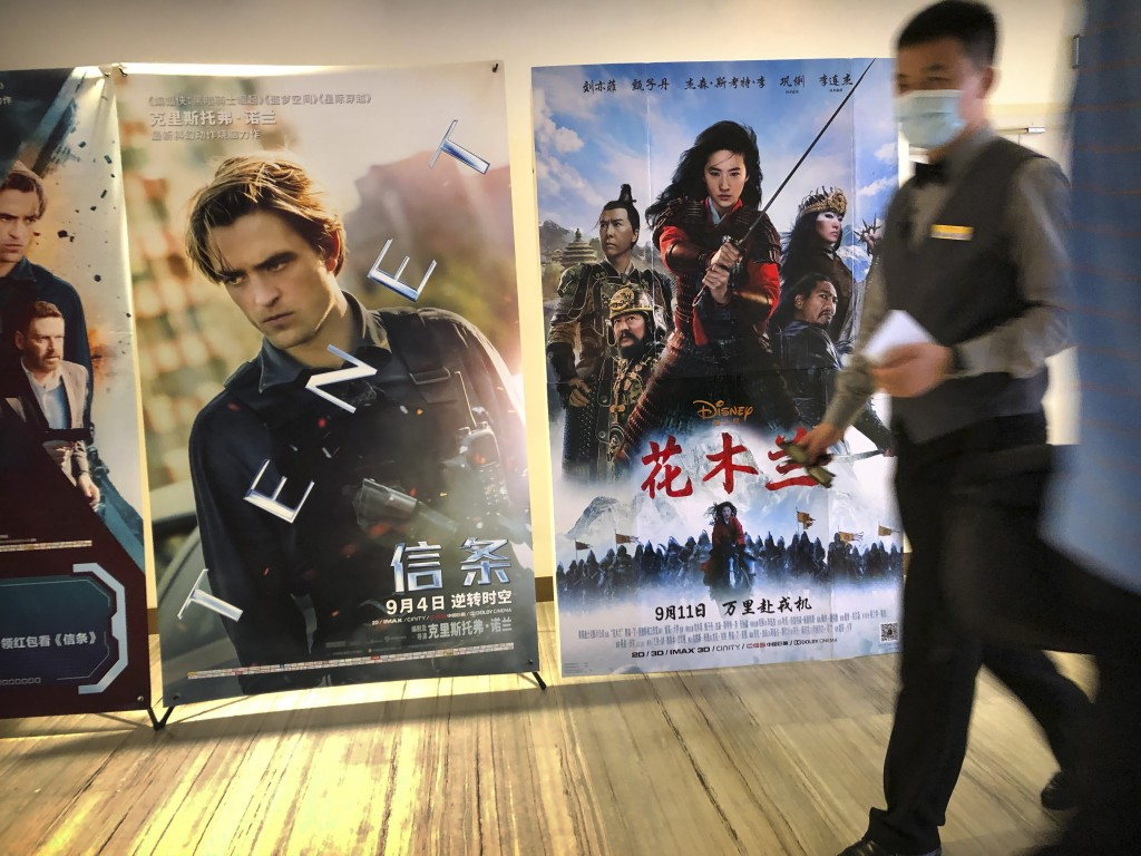 """An employee wearing a face mask walks past a poster for the Disney movie """"Mulan"""" at a movie theater in Beijing on Sept. 11, 2020. The remake of """"Mulan..."""