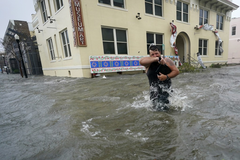 Trent Airhart wades through floodwaters, Wednesday, Sept. 16, 2020, in downtown Pensacola, Fla. Hurricane Sally made landfall Wednesday near Gulf Shor...