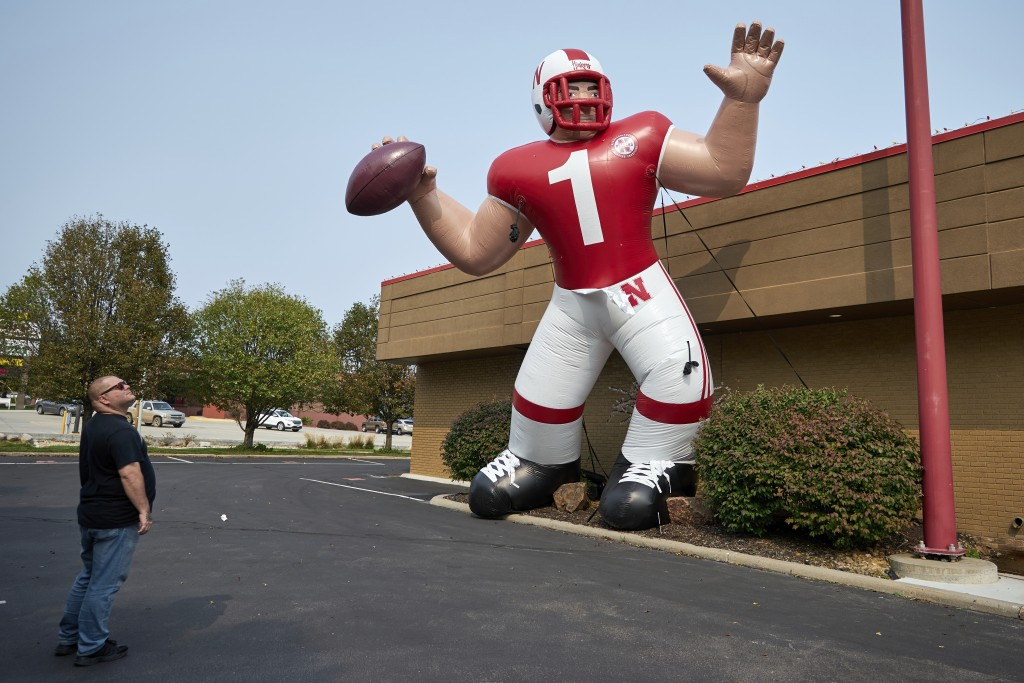 A Nebraska fan stops to look at a giant inflatable football player standing in front of the Husker Hounds sports apparel store in Omaha, Neb., Wednesd...