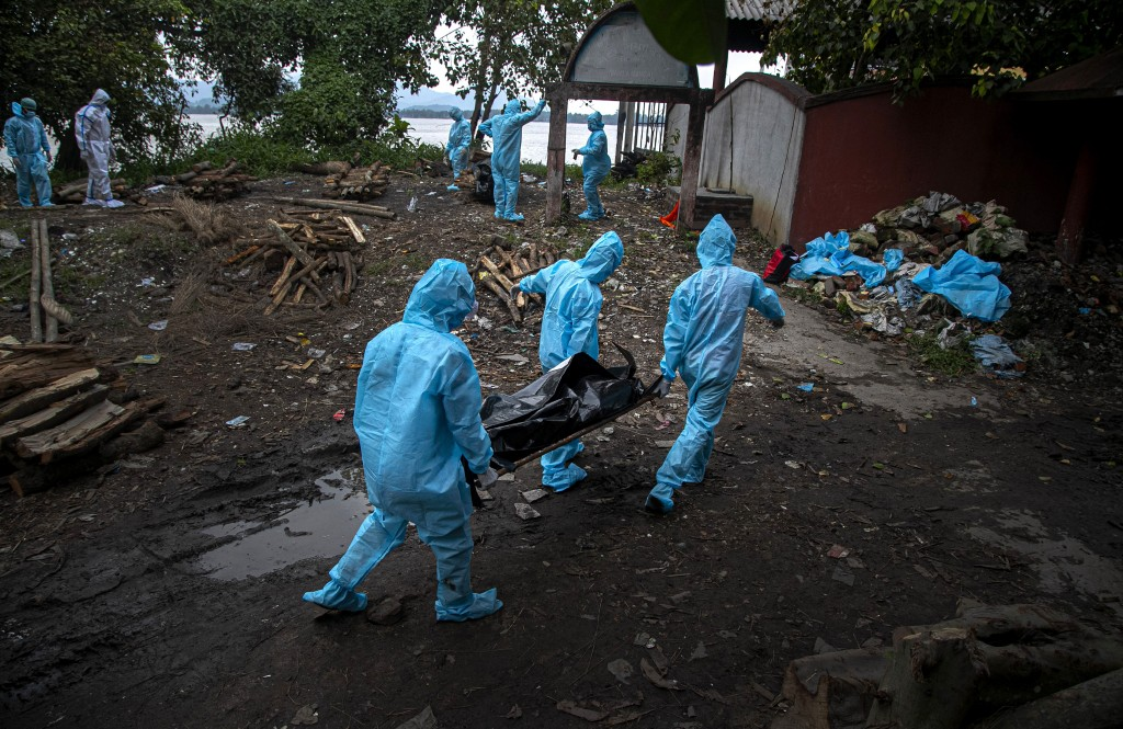 Health workers wearing personal protective equipment carry the body of a COVID-19 victim for cremation in Gauhati, India, Thursday, Sept. 10, 2020. In...