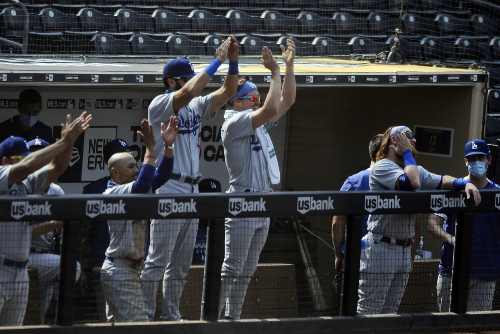 The Los Angeles Dodgers bench claps for Will Smith after he hit a two-run double against the San Diego Padres in the fifth inning of a baseball game W...