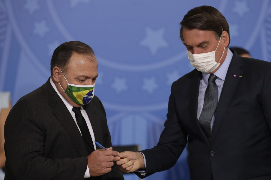 Brazil's President Jair Bolsonaro, wearing a mask to curb the spread of COVID-19, hands a pen to Health Minister Gen. Eduardo Pazuelo, left, at Planal...