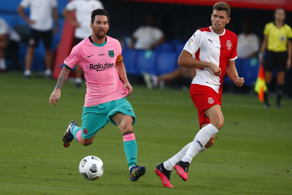 Barcelona's Lionel Messi, left, vies for the ball with Girona's Gumbau during the pre-season friendly soccer match between Barcelona and Girona at the...