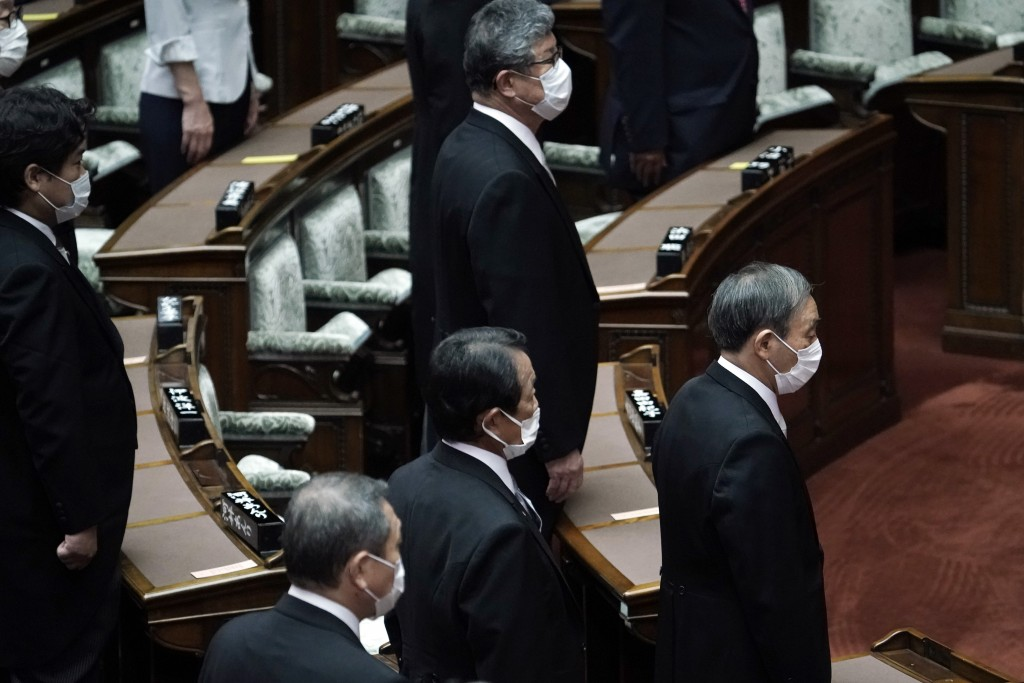 Japan's new Prime Minister Yoshihide Suga, right, attends an extraordinary session at the upper house of parliament Thursday, Sept. 17, 2020, in Tokyo...