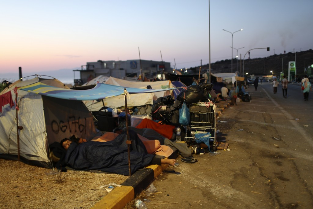 Migrants sleep outside their tents as they remained camped out on a road leading from Moria to the capital of Mytilene, on the northeastern island of ...