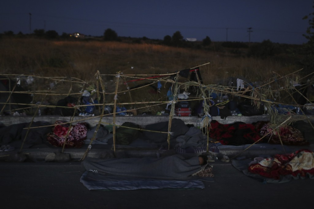 Migrants sleep as they remained camped out on a road leading from Moria to the capital of Mytilene, on the northeastern island of Lesbos, Greece, Thur...