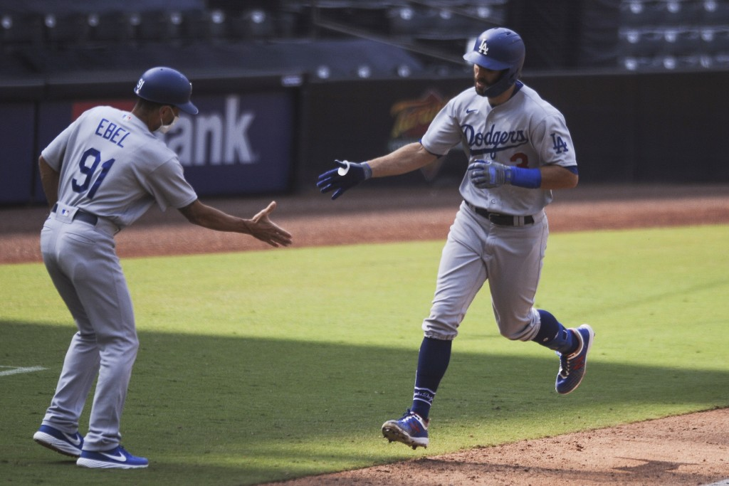 Los Angeles Dodgers' Chris Taylor is congratulated by Dino Ebel after hitting a solo home run off San Diego Padres relief pitcher Garrett Richards dur...