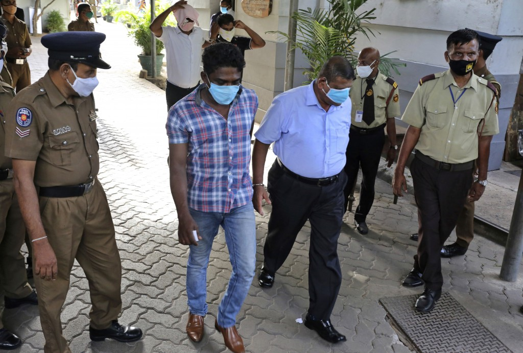 Sri Lankan police officials escort arrested narcotics unit police officers who are accused smuggling at a magistrate court in Colombo, Sri Lanka, on J...
