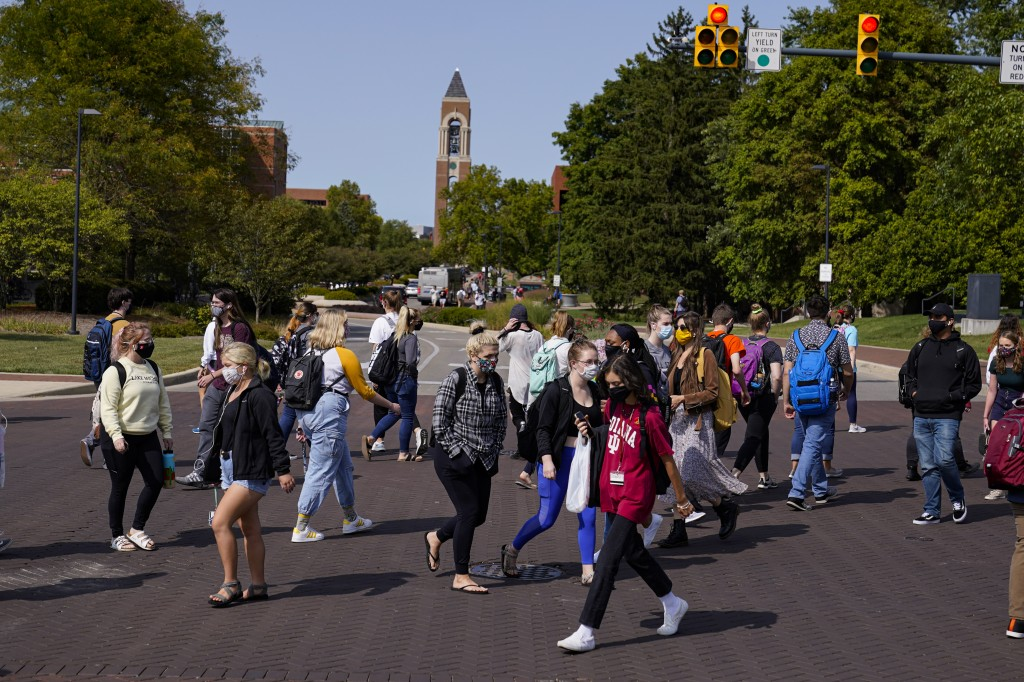 Masked students cross an intersection on the campus of Ball State University in Muncie, Ind., Thursday, Sept. 10, 2020. College towns across the U.S. ...