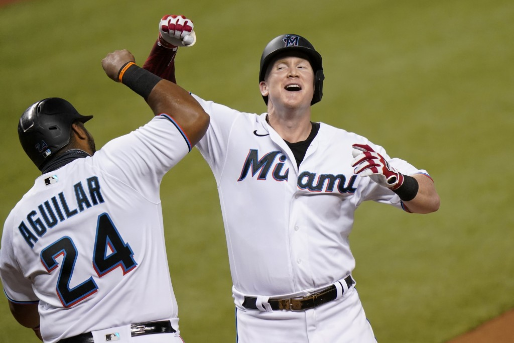 Miami Marlins' Garrett Cooper, right, celebrates with Jesus Aguilar (24) after hitting a two-run home run during the first inning of a baseball game a...