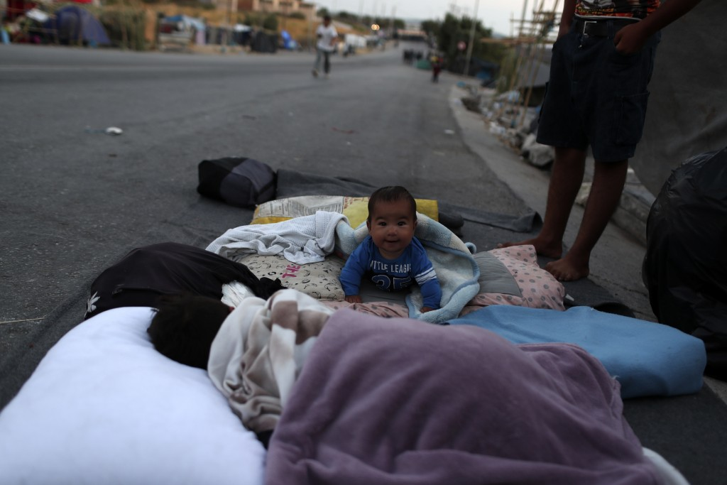A baby crawls as migrants remained camped out on a road leading from Moria to the capital of Mytilene, on the northeastern island of Lesbos, Greece, T...