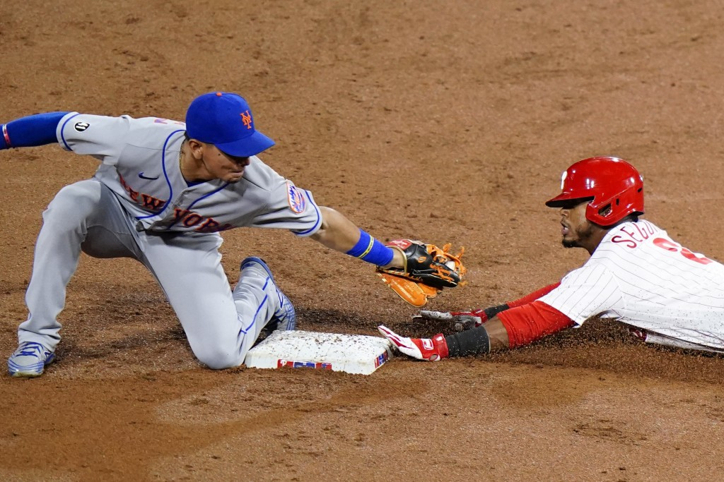 Philadelphia Phillies' Jean Segura, right, slides under the tag of New York Mets shortstop Andres Gimenez for a double during the second inning of a b...