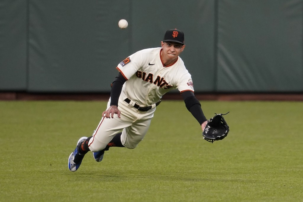 San Francisco Giants center fielder Mauricio Dubon cannot catch a base hit by Seattle Mariners' Dylan Moore during the first inning of a baseball game...