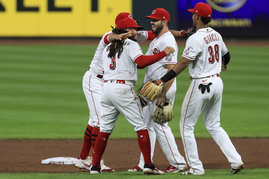 Cincinnati Reds' Joey Votto, back left, Freddy Galvis, second from left, Mike Moustakas, middle, and Jose Garcia celebrate after the Reds defeated the...