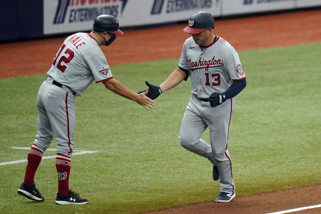 Washington Nationals' Asdrubal Cabrera (13) shakes hands with third base coach Chip Hale (12) after Cabrera hit a two-run home run off Tampa Bay Rays ...