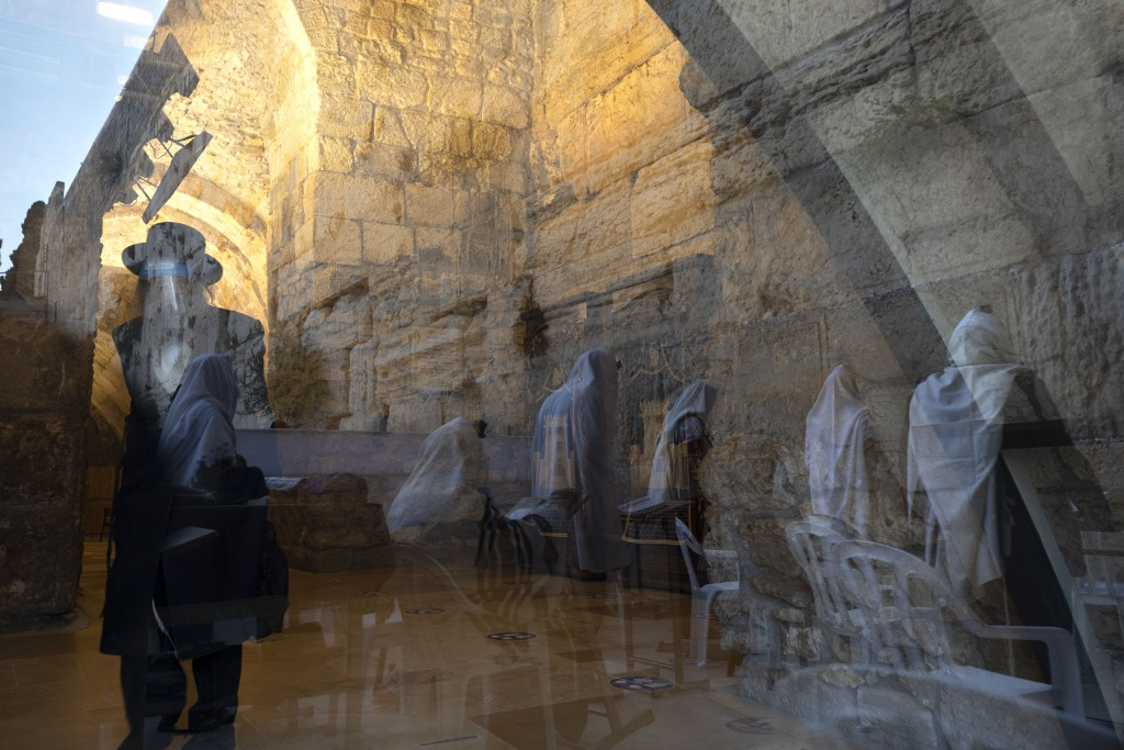 Ultra Orthodox Jewish men are seen reflected in a window as they pray ahead of the Jewish new year at the Western Wall, the holiest site where Jews ca...