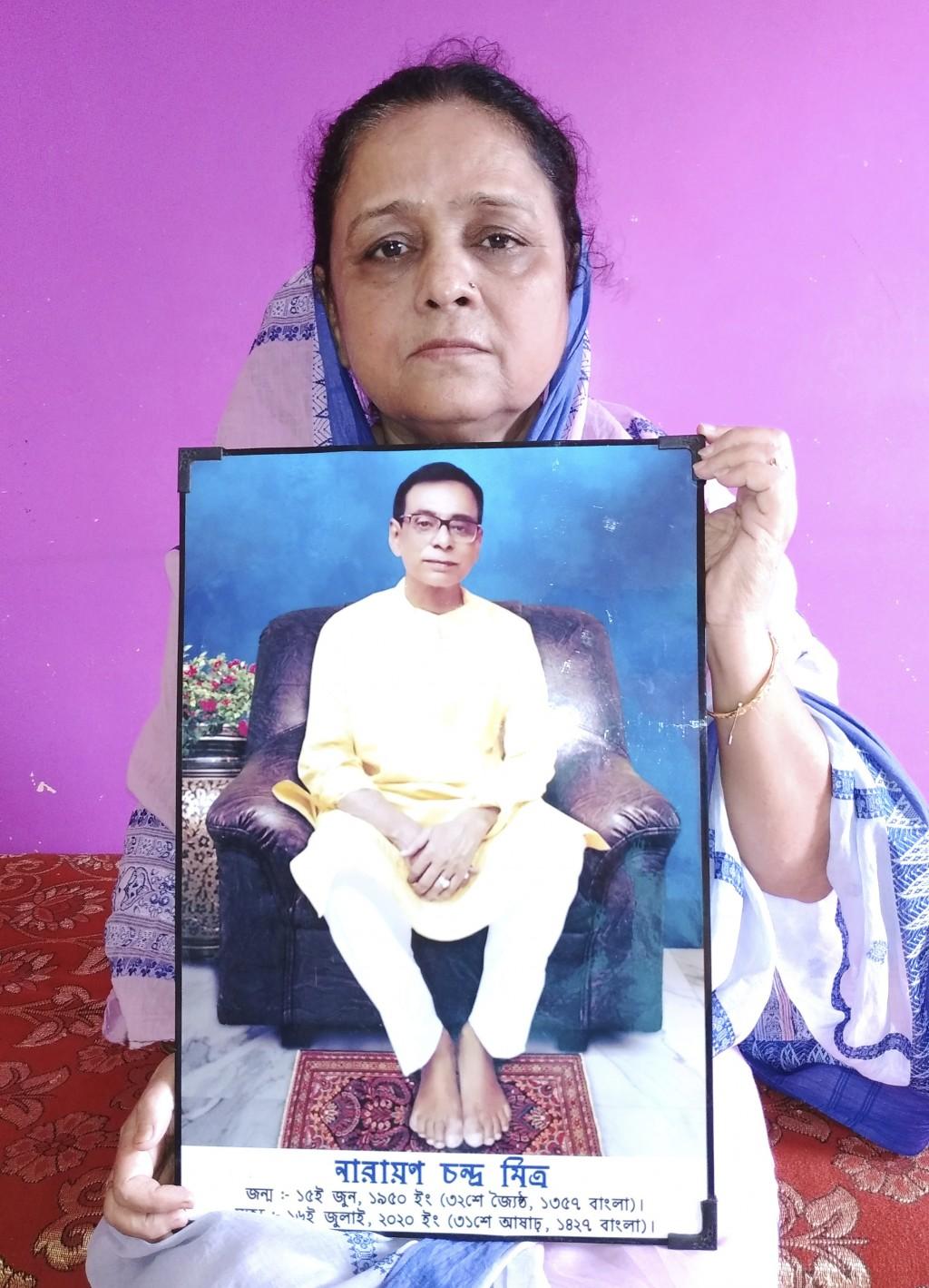 Anindita Mitra, 61, poses with a portrait of her husband late Narayan Mitra, at her house in Silchar, India, Sunday, Sept. 13, 2020. Narayan Mitra, wa...