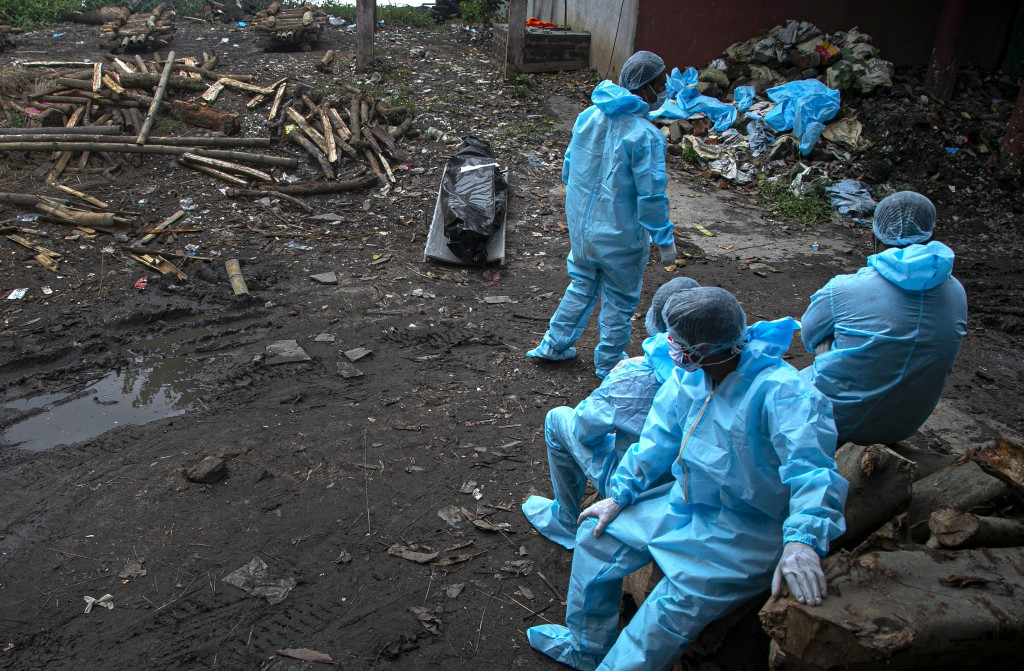 Health workers wearing personal protective equipment wait near the body of a person who died of COVID 19 at a cremation ground in Gauhati, India, Thur...