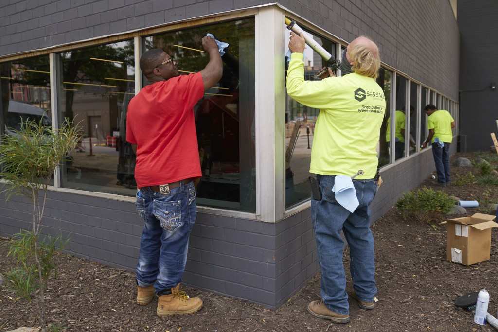 Workers replace windows smashed in May 2020, at a business in downtown Omaha, Neb., Wednesday, Sept. 16, 2020, one day after a grand jury decided to c...