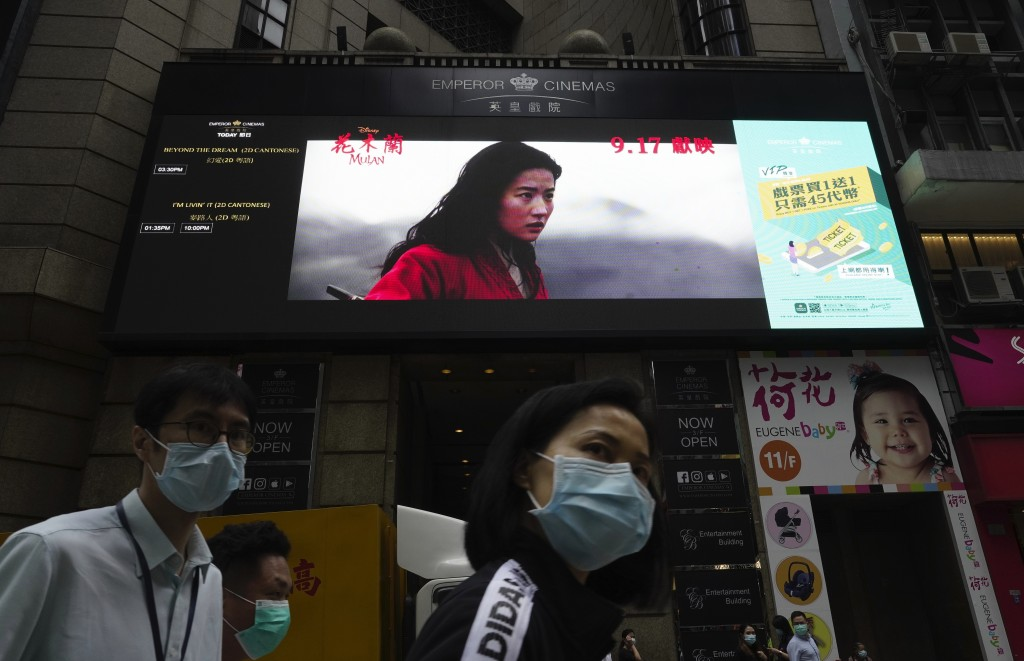 """People walk past a huge TV screen showing movie """"Mulan"""" at a downtown street in Hong Kong Thursday, Sept. 17, 2020. The remake of """"Mulan"""" struck all t..."""