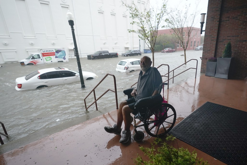 A man watches floodwaters, Wednesday, Sept. 16, 2020, in downtown Pensacola, Fla. Hurricane Sally made landfall Wednesday near Gulf Shores, Alabama, a...