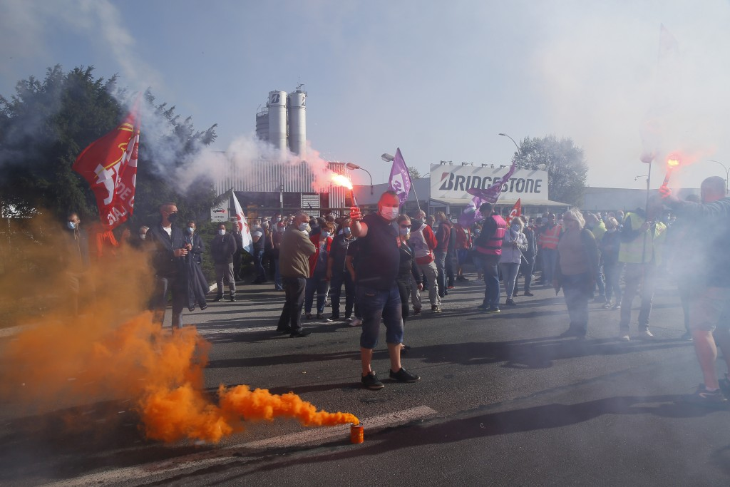 Bridgestone employees fire flares outside the tire factory of Bethune, northern France, Thursday, Sept.17, 2020. Workers protest over the Japan-based ...