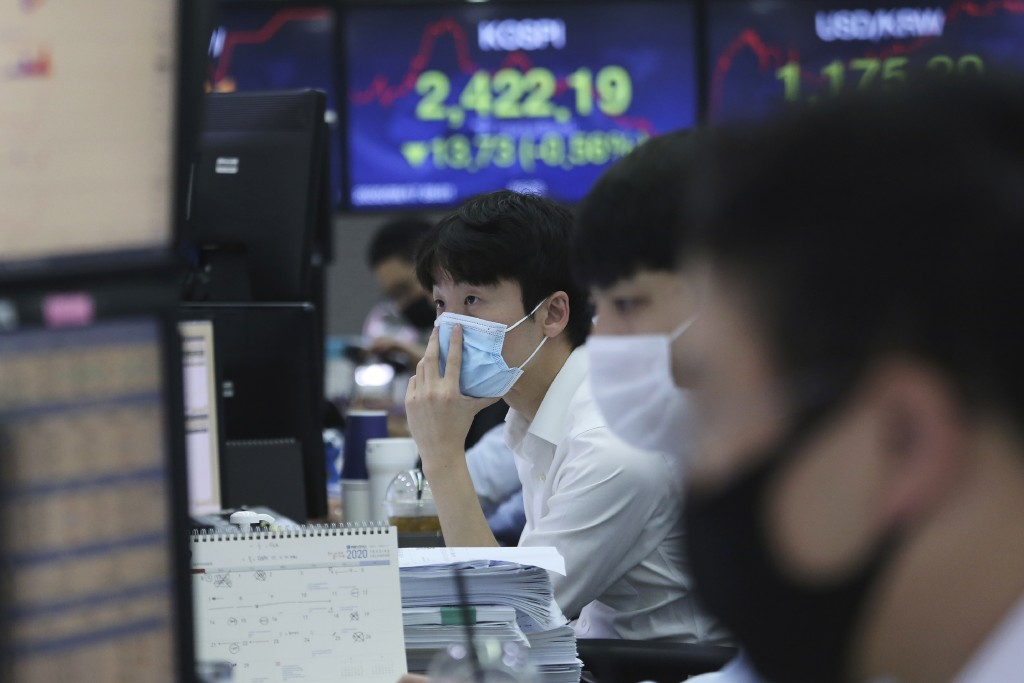 A currency trader watches monitors at the foreign exchange dealing room of the KEB Hana Bank headquarters in Seoul, South Korea, Thursday, Sept. 17, 2...
