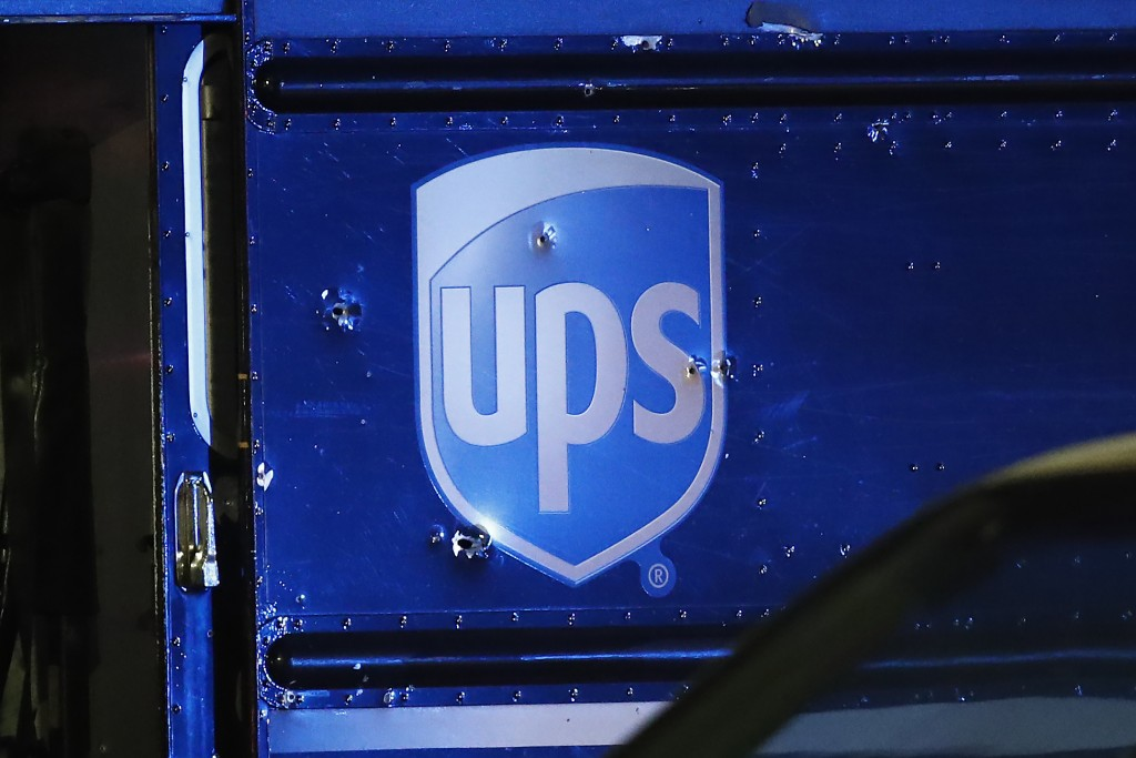 FILE- In this Dec. 5, 2019, file photo, bullet holes are seen around the UPS logo of a truck at the scene of a shooting that killed four people, inclu...