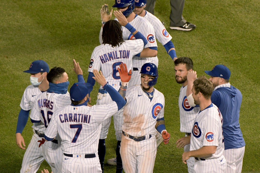 Chicago Cubs' Javier Baez (9) celebrates with teammates after driving in the winning run during the 10th inning against the Cleveland Indians in a bas...