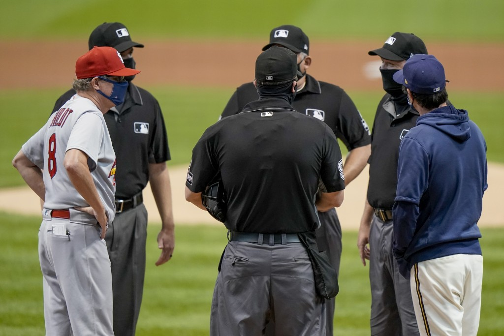 St. Louis Cardinals manager Mike Shildt and Milwaukee Brewers manager Craig Counsell talk to the umpires before the first game of a baseball doublehea...