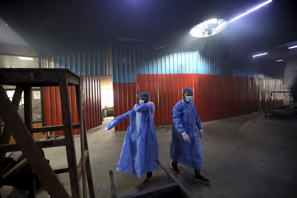 Workers put on personal protective suits before carrying the body of a COVID-19 victim for cremation in New Delhi, India, Wednesday, Sept. 16, 2020. I...