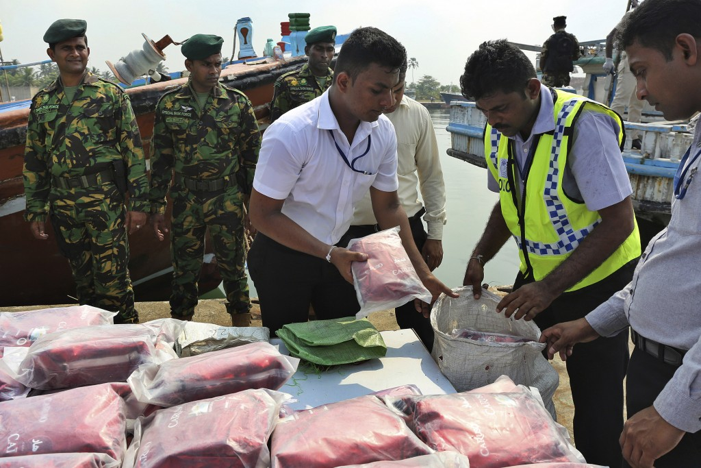 Sri Lankan police officers belonging to the narcotics unit stack up a seized haul of narcotics at a fishery harbor in Colombo, Sri Lanka, on May 3, 20...