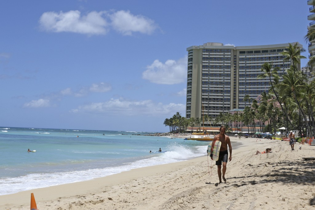 FILE - In this June 5, 2020, file photo, a surfer walks on a sparsely populated Waikiki Beach in Honolulu. Hawaii's governor says that starting Oct. 1...