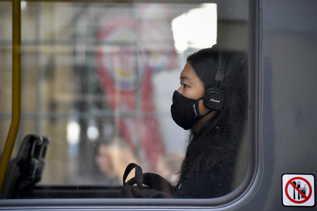 A young woman with face mask is sitting in a tram  in Prague, Czech Republic, Thursday, Sept. 17, 2020 The number of new confirmed coronavirus infecti...