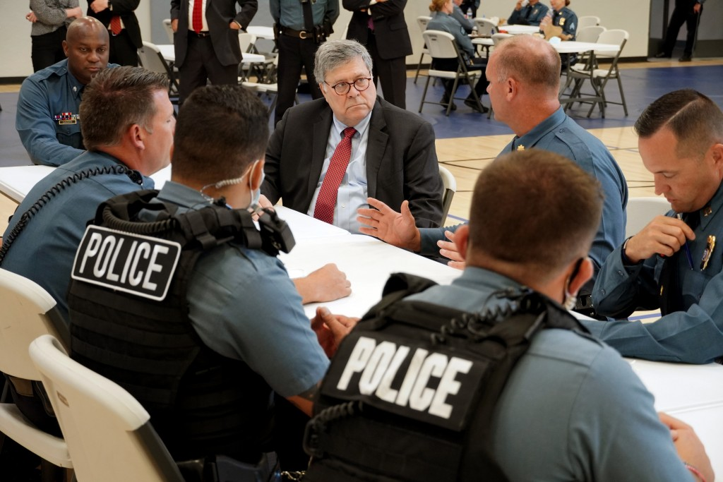 FILE - In this Aug. 19, 2020, photo Attorney General William Barr participates in a roll call with police officers from the Kansas City Police Departm...