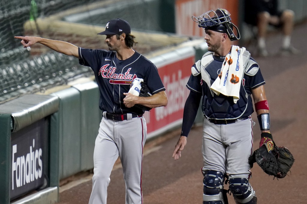 Atlanta Braves starting pitcher Cole Hamels, left, gestures to teammates sitting in the stands while walking with catcher Tyler Flowers to the dugout ...