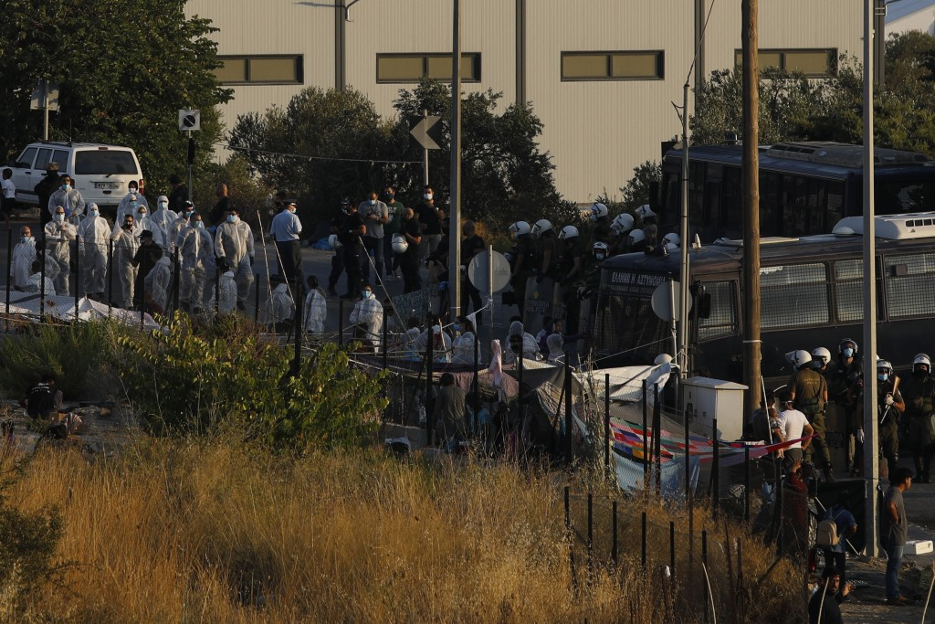 Riot police with buses block the access as their colleagues with special suits to protect against coronavirus, take part in operation to evacuate a ro...