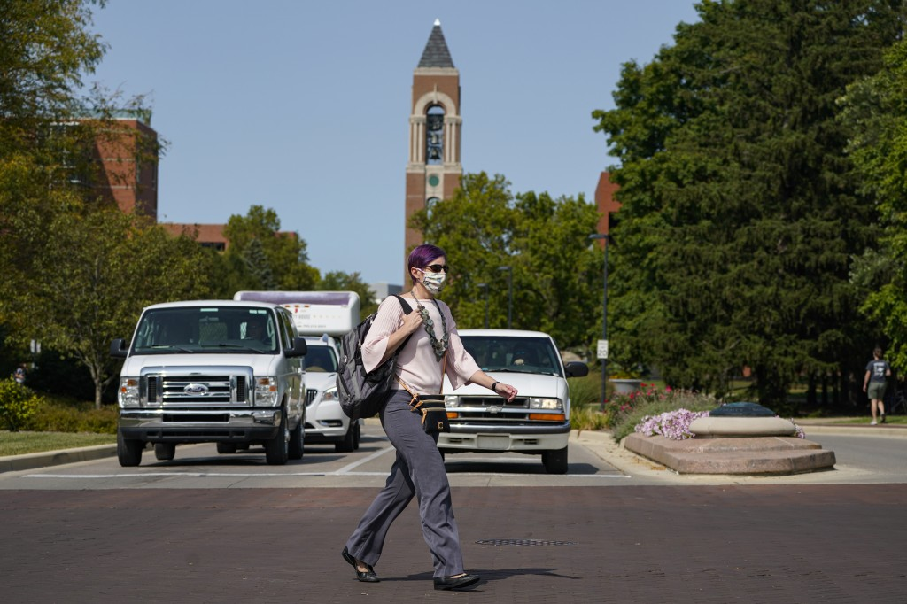 A masked student crosses a street on the the campus of Ball State University in Muncie, Ind., Thursday, Sept. 10, 2020. College towns across the U.S. ...