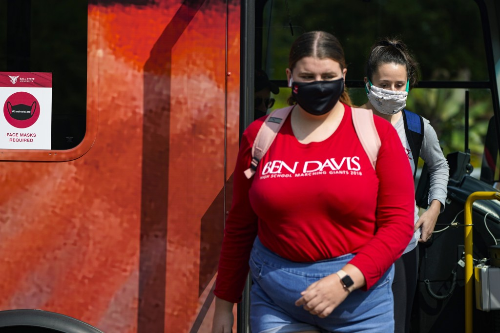 FILE - Masked students disembark from a bus on the campus of Ball State University in Muncie, Ind., Thursday, Sept. 10, 2020.    Colleges across the c...