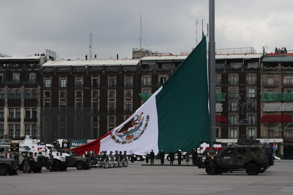 Soldiers raise a Mexican national flag as part of its annual Independence Day military parade, on the Zocalo, the main plaza in Mexico City, Wednesday...