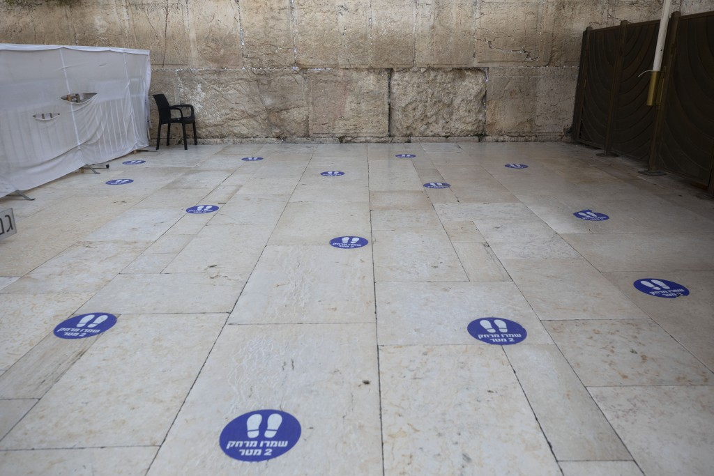 Marks to keep a 2-meter distance are seen on the floor at the Western Wall, the holiest site where Jews can pray in Jerusalem's old city, Wednesday, S...