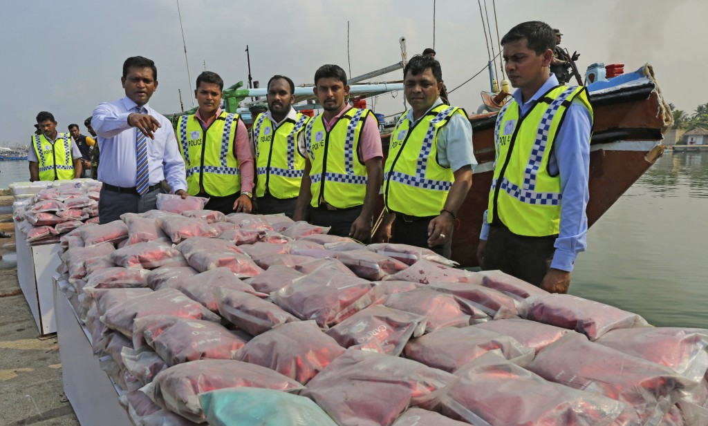 Sri Lankan police officers belonging to the narcotics unit, in green jackets, stand next to a seized haul of narcotics at a fishery harbor in Colombo,...